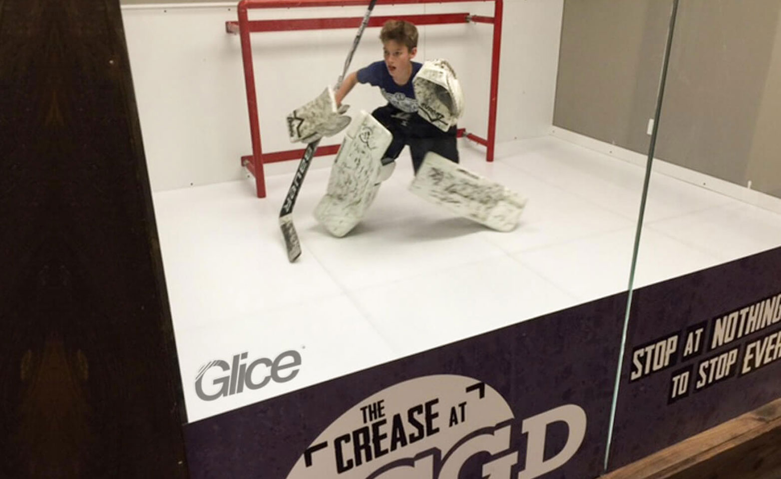 Child as a hockey goalie on artificial ice pad