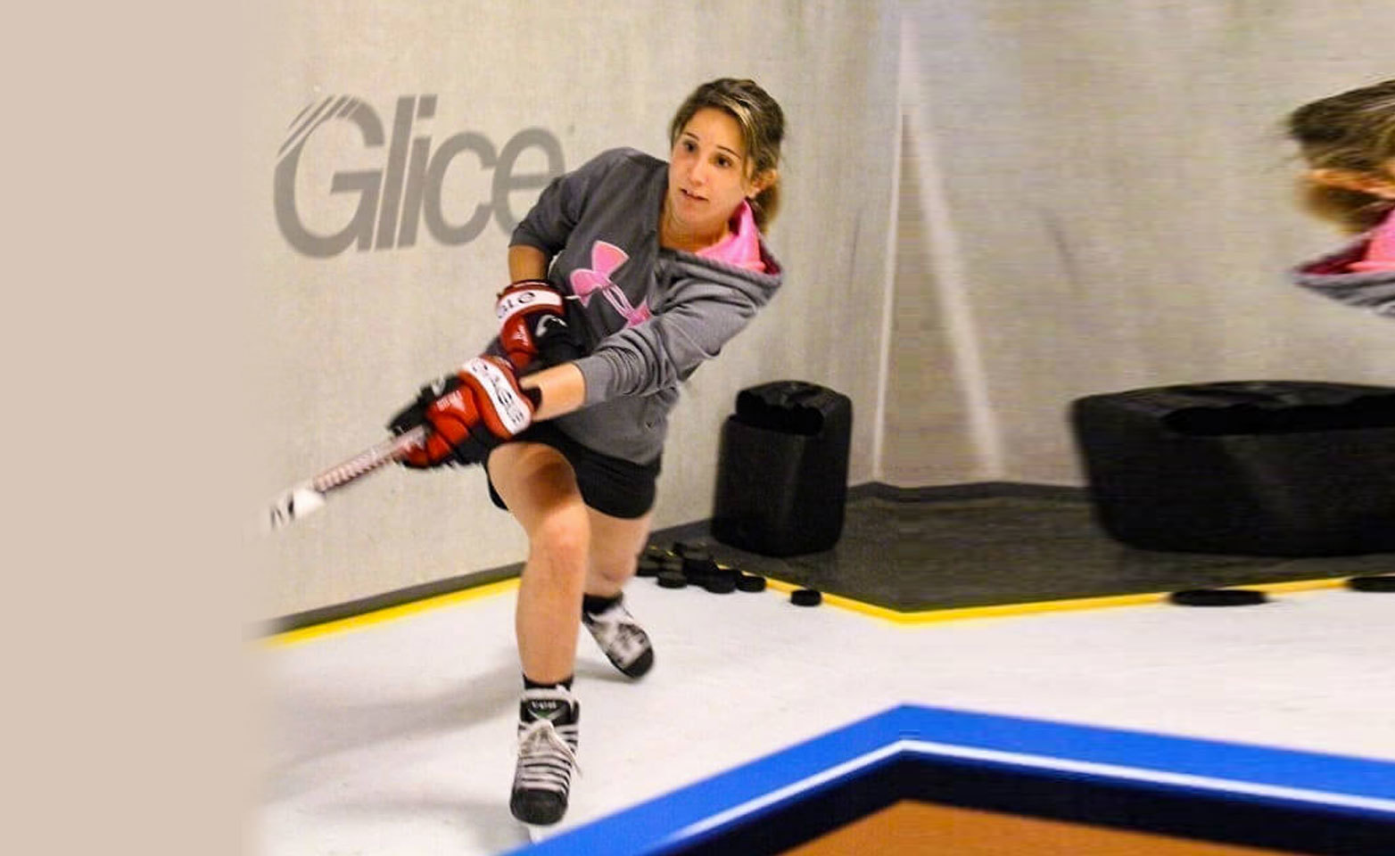 Female hockey player practicing on synthetic ice pad